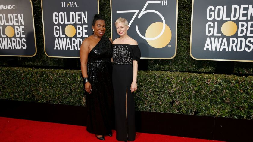 Tarana Burke, who founded the Me Too movement in 2006, left, and actress Michelle Williams appear on the red carpet at the 75th Golden Globes at the Beverly Hilton Hotel on Sunday.