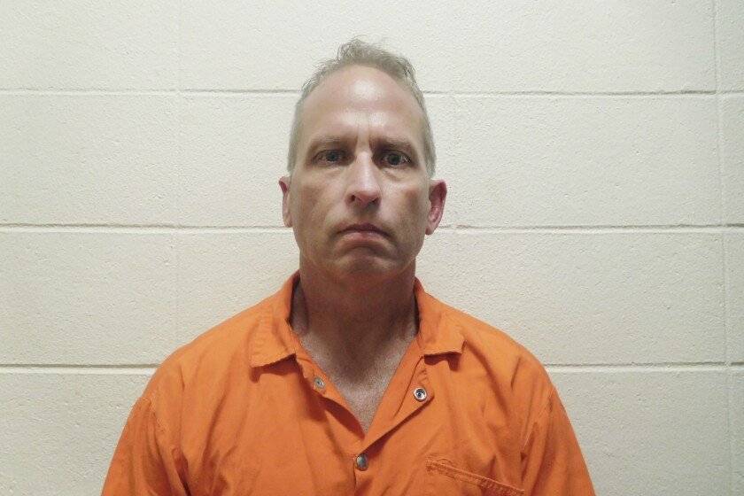 A booking photo of a man in an orange jumpsuit
