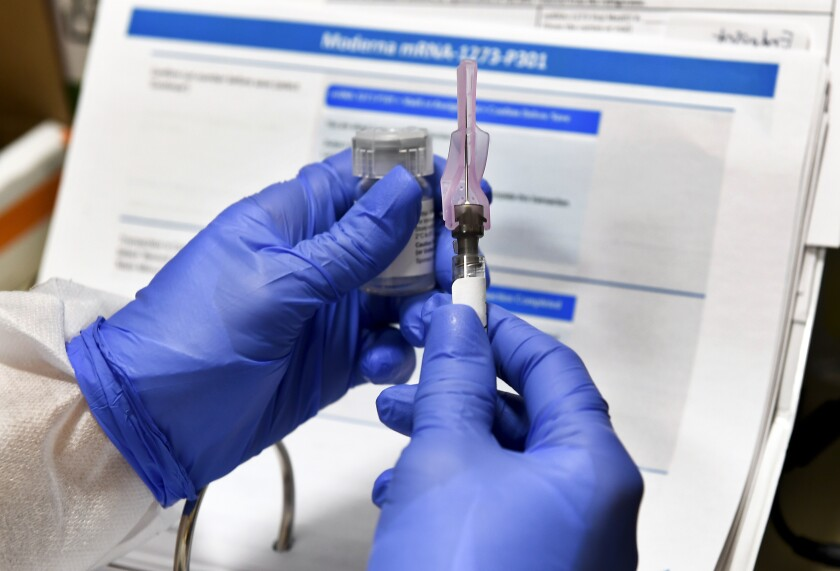 A nurse prepares a shot that is part of a possible COVID-19 vaccine.
