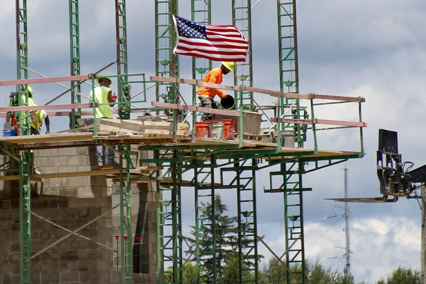FILE - In this June 11, 2020 file photo, workers on scaffolding lay blocks on one of the larger buildings at a development site where various residential units and commercial sites are under construction in Cranberry Township, Butler County, Pa. U.S. productivity increased at a solid 4.6% pace in the July-September quarter, slightly below the initial estimate, while labor costs fell at a slower pace. The Labor Department reported that the third quarter increase in productivity was below the first estimate a month ago of a 4.9% increase. (AP Photo/Keith Srakocic, File)