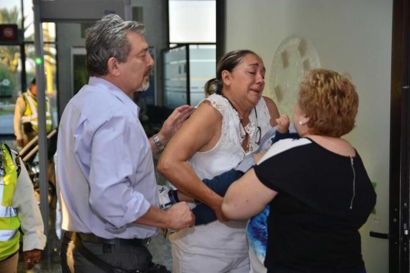 Rosa María Santamans (d), madre de Pilar Garrido, recibe a su nieto de un año de manos de Adriana González (c) y Jorge Fernández Villareal (i), padres del esposo de Pilar, Jorge Fernández. EFE/Archivo