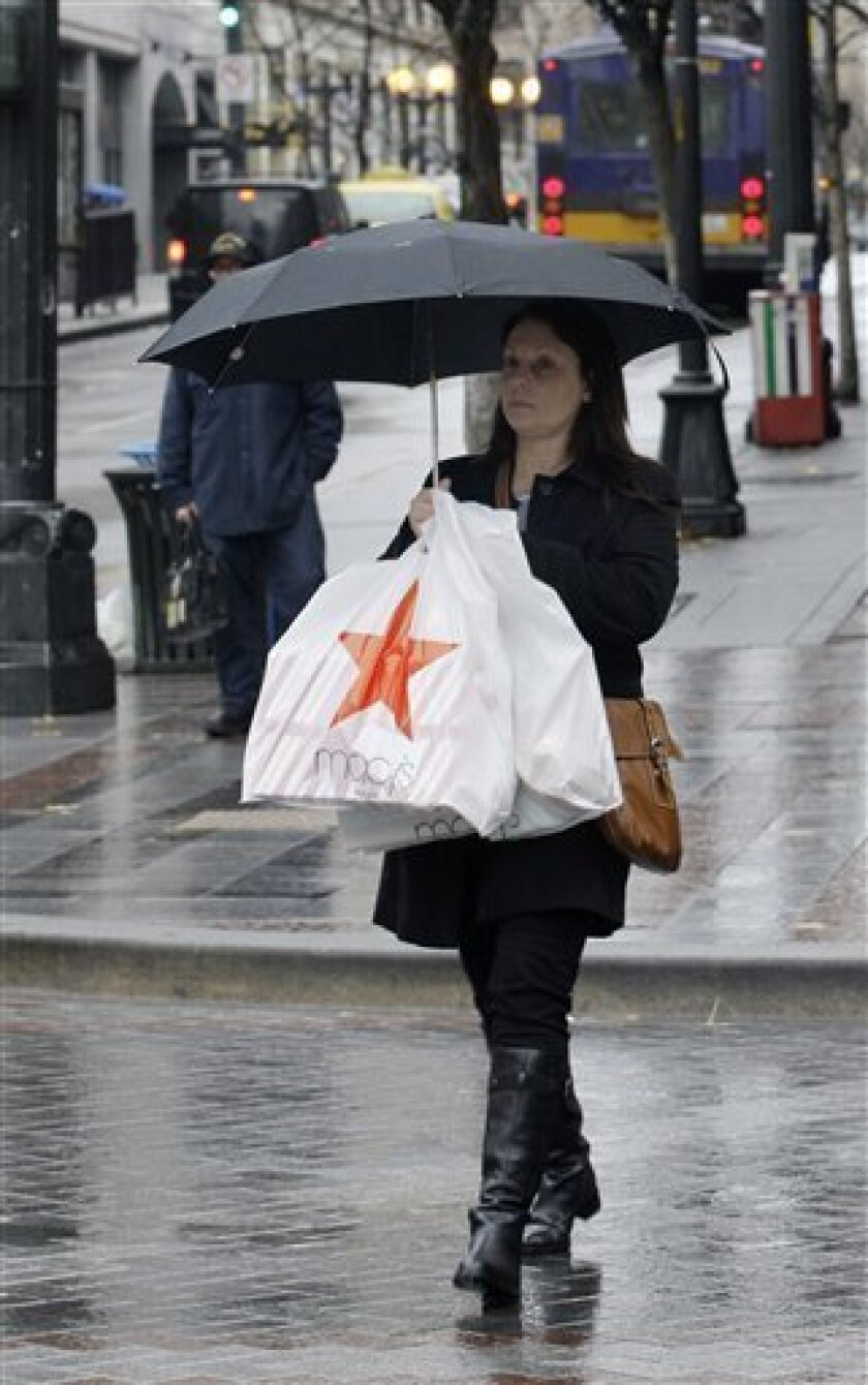 A shopper uses an umbrella to shield herself and her purchases from the rain, Tuesday, Dec. 9, 2008, in downtown Seattle. Consumers cut back on spending at retail stores for a record fifth straight month in November, another sign the recession that is already the longest in a quarter-century will translate into a dismal holiday shopping season. (AP Photo/Ted S. Warren)