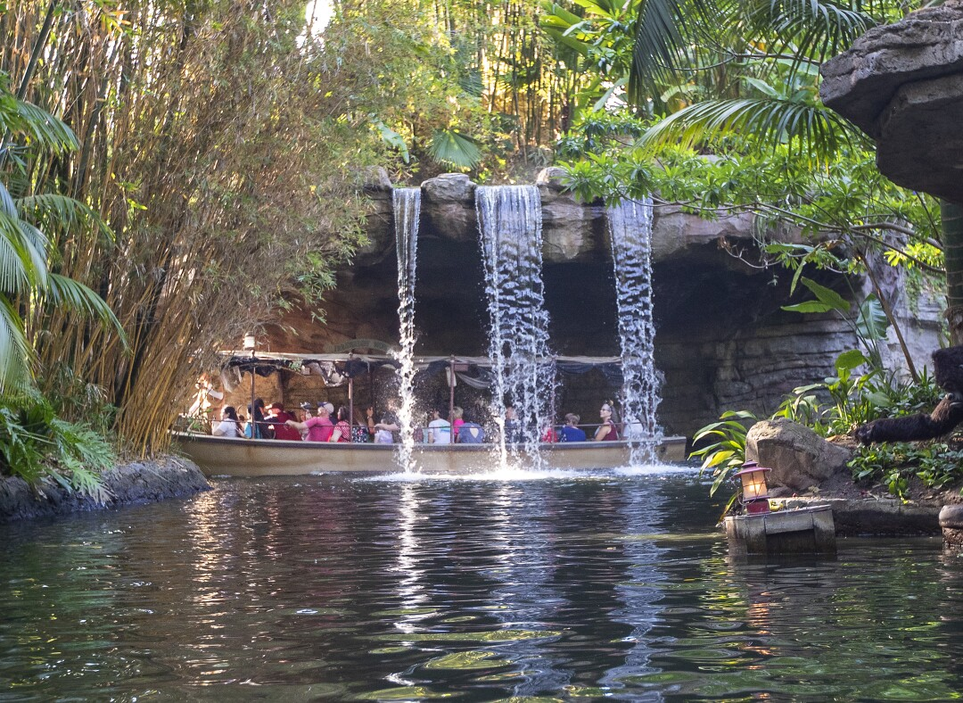 Riders pass under waterfalls at Schweitzer Falls during the Jungle Cruise ride.