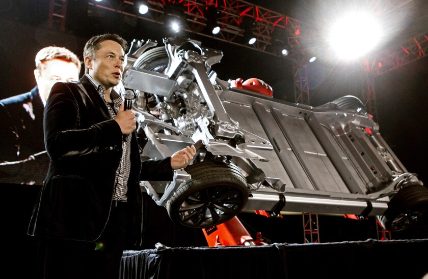 Elon Musk shows off the undercarriage of a Tesla auto in this 2014 file photo. But what's under the hood of his offer for SolarCity?