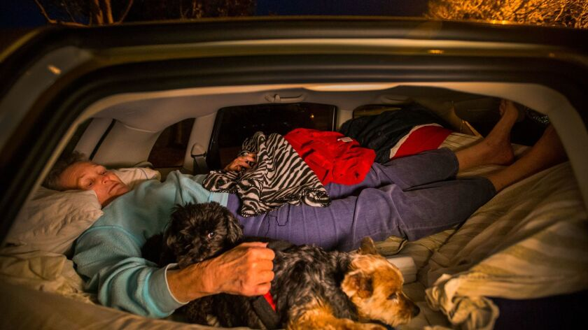"""After the Carlsbad Senior Center closed for the night, Edythe Russell, 79, tucks into the back of her car on an air mattress to sleep with her two """"children"""" dogs Chloe, right, and Tippy."""