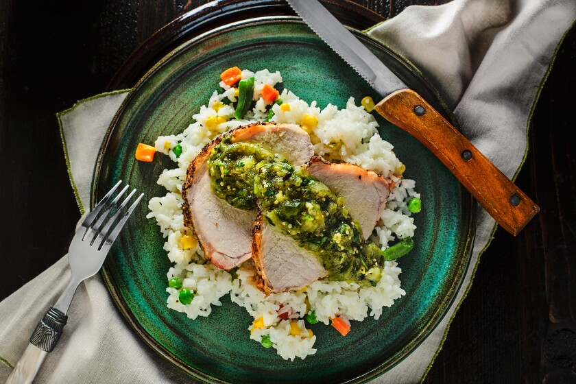 Easy-to-make pork loin with chunky salsa verde, served on a bed of rice with mixed vegetables.