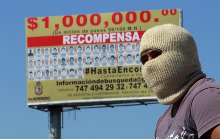 Fotografía de archivo del 27 de octubre de 2014 que muestra a un estudiante de la escuela de Ayotzinapa junto a un anuncio panorámico donde se ofrece una recompensa por los 43 estudiantes desaparecidos, en la ciudad de Chilpancingo, en el estado de Guerrero (México). EFE/Archivo