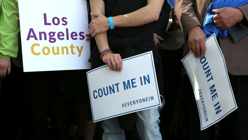 "Members of the crowd hold signs as they listen to speakers during the launch of ""Everyone In,"" a campaign to bring people throughout L.A. County together around the goal of ending homelessness."
