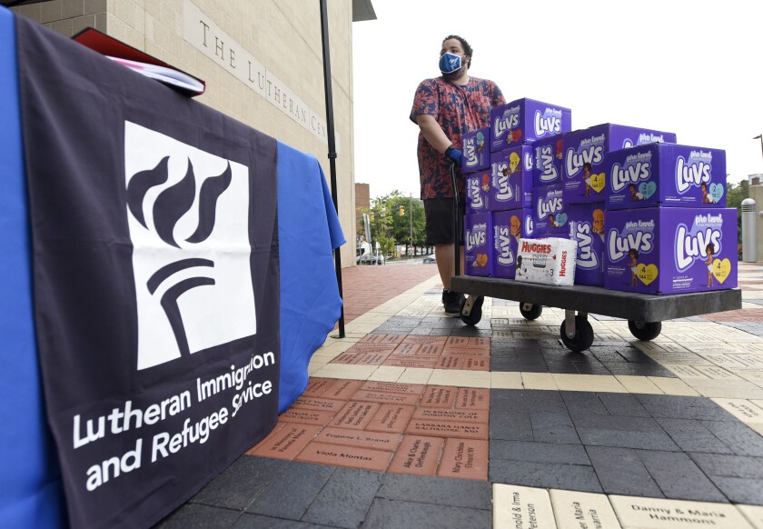 """A masked person rolls a cart of Luvs diapers past a sign reading """"Lutheran Immigration and Refugee Service"""""""