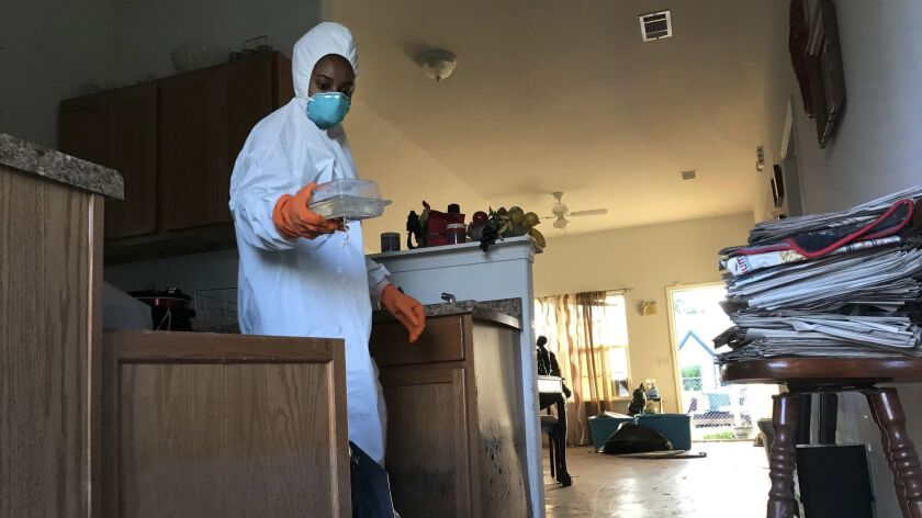 Corinth Williams, 28, discards kitchenware as she helps clean out her grandmother's house in Port Arthur.