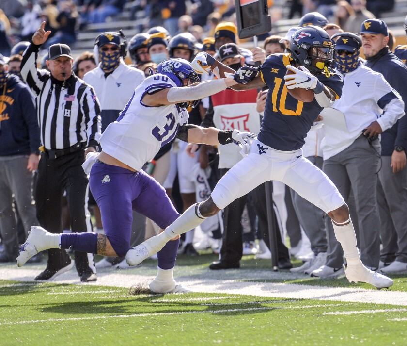 West Virginia wide receiver Sean Ryan (10) is pushed out of bounds by TCU linebacker Garret Wallow (30) during the first half of an NCAA college football game on Saturday, Nov. 14, 2020, in Morgantown, W.Va. (William Wotring/The Dominion-Post via AP)