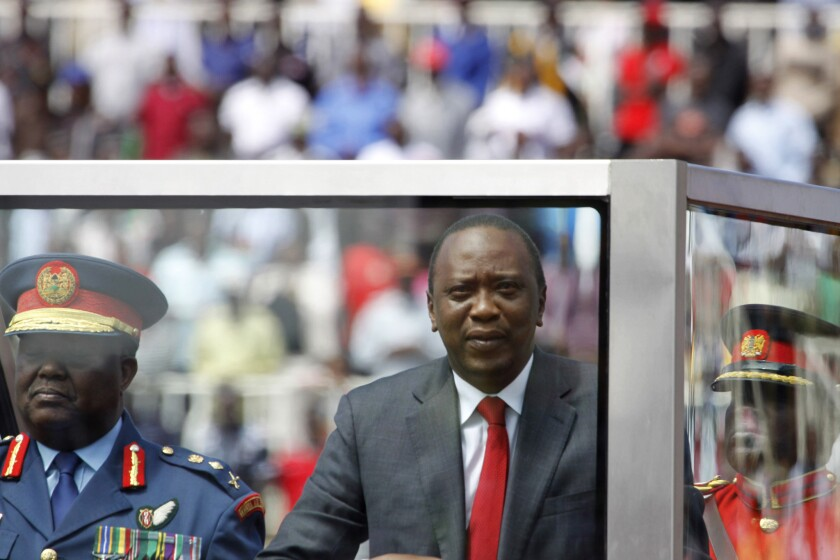 Kenyan President Uhuru Kenyatta, center, shown at a public celebration earlier in the month, denied June 17 that two attacks along the Kenyan coast were carried out by Somali militants, saying instead that local leaders were to blame.
