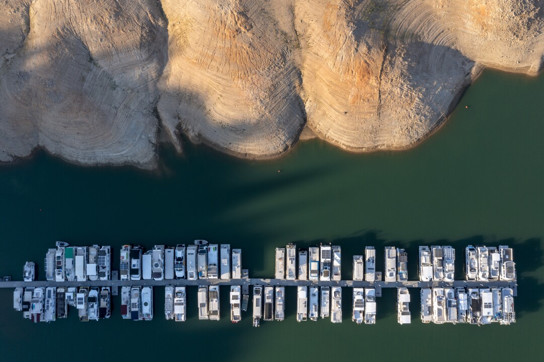 Boats are tied up at a Lake Shasta marina, hundreds of feet below where they are usually moored.