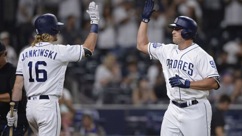 The Padres' Hunter Renfroe is greeted at home plate after hitting a home run by Travis Jankowski during the eighth inning of a baseball game against the Arizona Diamondbacks Thursday, Aug. 16, 2018, in San Diego.