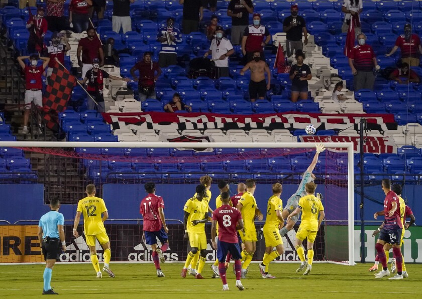 Socially distant FC Dallas supporters watch as a free kick by FC Dallas midfielder Bryan Acosta (8) sails over the bar and Nashville SC goalkeeper Joe Willis on the final play in added time of an MLS soccer game, Wednesday, Aug. 12, 2020, in Frisco, Texas. Nashville SC won the game 1-0. (Smiley N. Pool/The Dallas Morning News via AP)