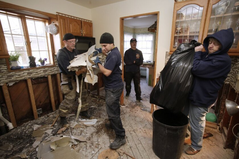 New Orleans firefighter Bruce Hurley Sr., left, and New York firefighter John Militano clear Sheetrock from a gutted kitchen as homeowner Colleen Dwyer, right, bags debris in her home flooded in Superstorm Sandy in the Belle Harbor section of Queens, N.Y., on Wednesday. Sandy, which hit the Northeast hard, was the reason jobless claims spiked