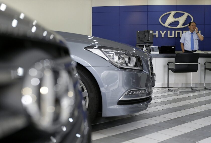 An employee of Hyundai Motor Co. works at the company's showroom in Seoul, South Korea, Thursday, July 23, 2015. Hyundai Motor Co. says its second quarter earnings sank 24 percent due to a sales drop in China and weakness in other markets due to falling currencies.(AP Photo/Ahn Young-joon)