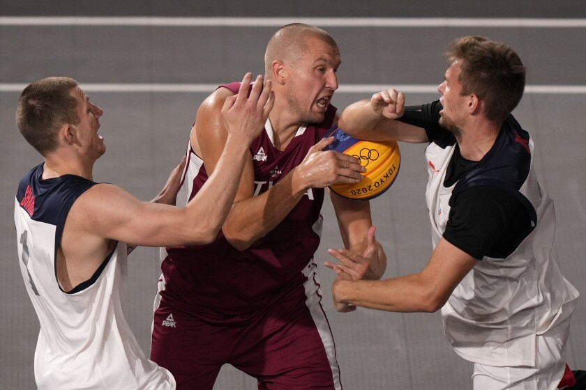 Edgars Krumins, center, of Latvia, is pressured by Stanislav Sharov (1) and Alexander Zuev, right, of the Russian Olympic Committee, during a men's 3-on-3 basketball game at the 2020 Summer Olympics, Monday, July 26, 2021, in Tokyo, Japan. (AP Photo/Charlie Riedel)