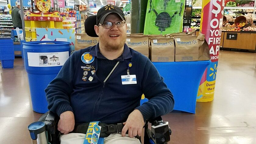 In this April 21, 2018 photo provided by Rachel Wasser, Walmart greeter John Combs works at a Walmar
