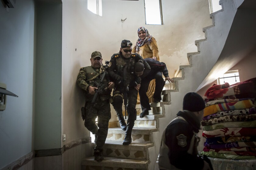 Iraqi security forces drag a suspected Islamic State fighter down a spiral staircase after raiding his house in the liberated eastern part of Mosul on Feb. 21, 2017.