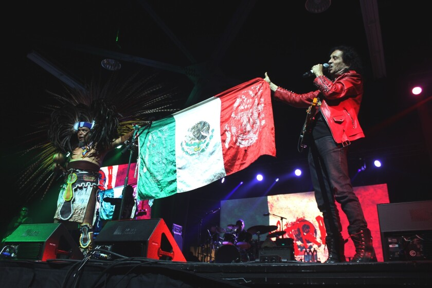 Álex Lora, cantante y guitarrista de El Tri, levanta una bandera mexicana durante el festival rockero La Tocada