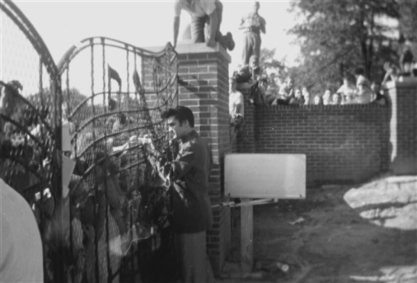 In this 1957 photo provided by Elvis Presley Enterprises, Inc and used by permission, Elvis Presley greets fans at the gates of Graceland in Memphis, Tenn. Elvis Presley archivists have found three rare photos dating back to 1957 that show the young singer greeting fans at the gates of Graceland. Negatives of the photos were discovered as archivists pored through a vast collection of documents from the office of Vernon Presley, Elvis' father. (AP Photo/Elvis Presley Enterprises, Inc) NO SALES