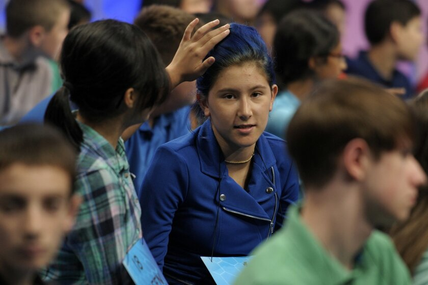 Colleen Ung, 13, of San Bernardino, left, touches the blue hair of Oona Flood, 14, of Solana Beach as they wait for the 2015 Scripps National Spelling Bee to resume after a lunch break in Oxon Hill, Md., Wednesday, May 27, 2015. (AP Photo/Cliff Owen)