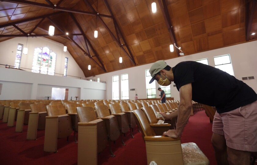 Alamo Heights Baptist Church pastor Bobby Contreras works to clean, sanitize and prepare his church for services in San Antonio, Texas.