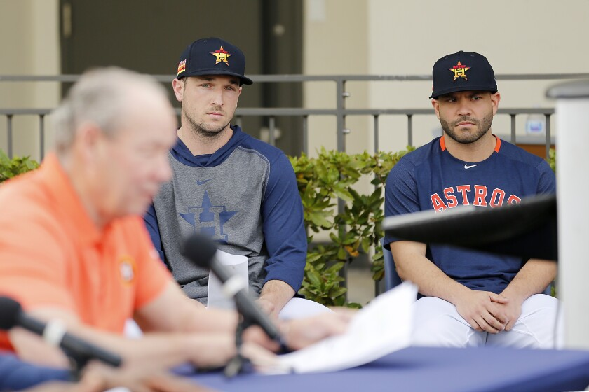 Alex Bregman and Jose Altuve, right, look on as Houston Astros owner Jim Crane reads a prepared statement during a news conference Feb. 13.