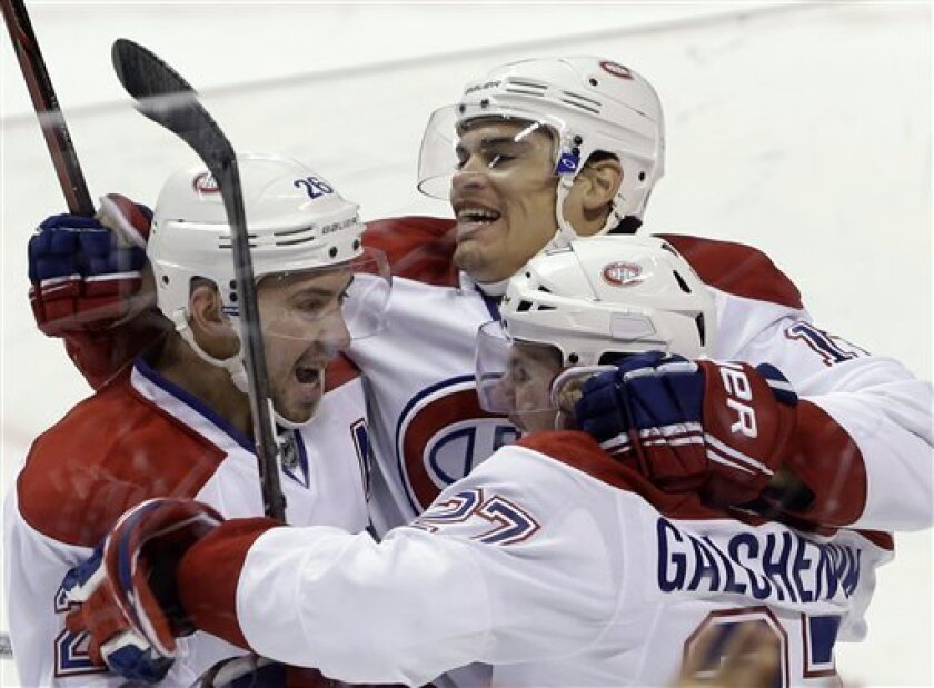 Montreal Canadiens left wing Rene Bourque, center, celebrates with defenseman Josh Gorges, left, and center Alex Galchenyuk after Bourque scored against the Florida Panthers during overtime in an NHL hockey game, Thursday, Feb. 14, 2013 in Sunrise, Fla. The Canadiens won 1-0. (AP Photo/Wilfredo Lee)