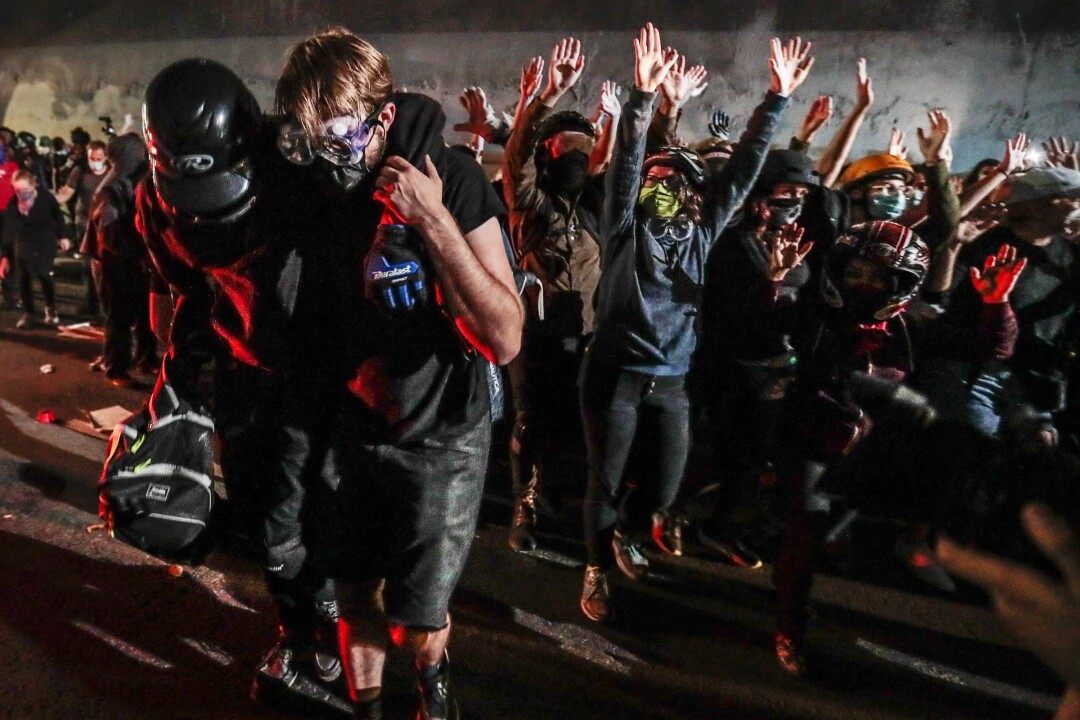 A comrade helps an injured protester in a confrontation with LAPD officials in the 3rd Street tunnel.