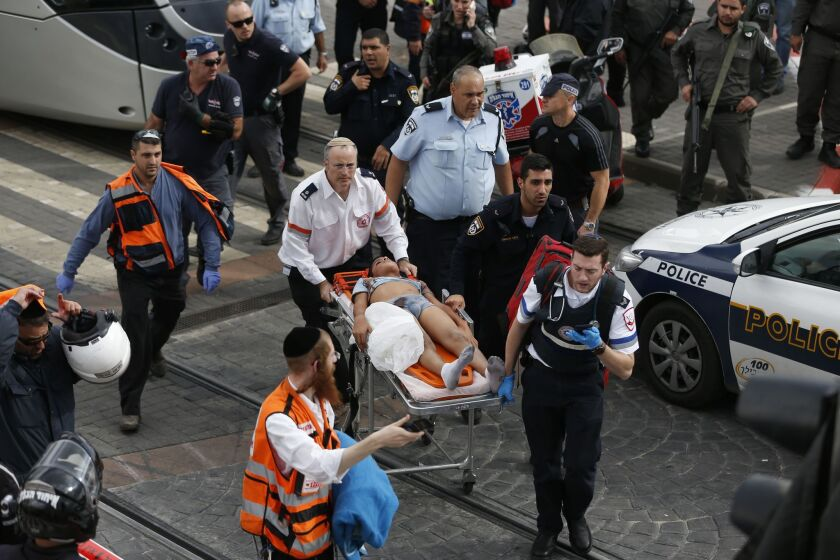 Israeli paramedics and security forces evacuate a wounded Palestinian boy who was shot after an Israeli security guard was stabbed at a tramway station in the neighbourhood of Pisgat Zeev in East Jerusalem on Nov. 10, 2015..