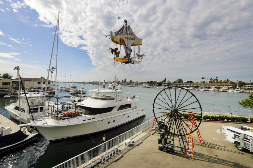 A boat parade decoration is lowered by crane onto a yacht in Newport Beach.