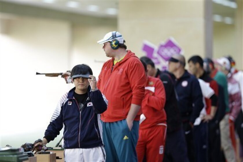 South Korea's Choi Young Rae, front, concentrates between shots during qualifiers for the men's 50-meter pistol event, at the 2012 Summer Olympics, Sunday, Aug. 5, 2012, in London. (AP Photo/Rebecca Blackwell)