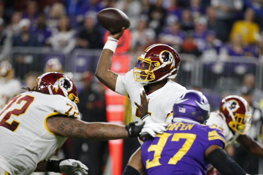 Washington Redskins quarterback Dwayne Haskins, center, throws a pass during the second half of an NFL football game against the Minnesota Vikings, Thursday, Oct. 24, 2019, in Minneapolis. (AP Photo/Bruce Kluckhohn)