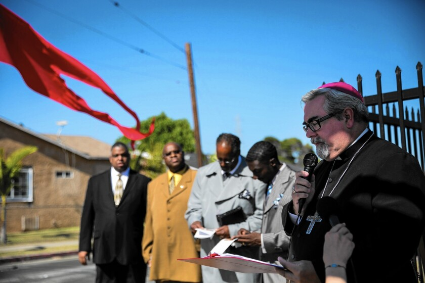 Bishop Guy Erwin of the Evangelical Lutheran Church in America, far right, says a prayer at an interfaith service marking the 50th anniversary of the Watts riots on Sunday.