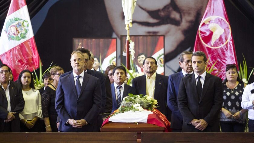 Jorge Munoz, left, the mayor of Lima, Peru, and Venezuelan Ambassador Carlos Scull, right, attend a wake for former Peruvian President Alan Garcia in Lima on Thursday.