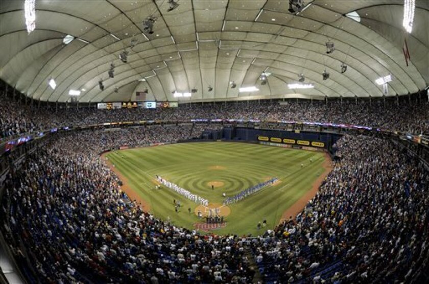 Minnesota Twins and Kansas City Royals line-up on the base lines during the national anthem prior to their baseball game Sunday, Oct. 4, 2009 in Minneapolis. This is the last regular season game that will be played at the Hubert H. Humphrey Metrodome. (AP Photo/Tom Olmscheid)