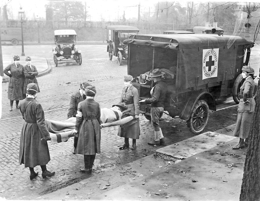 Red Cross members remove flu victims from a house in 1918