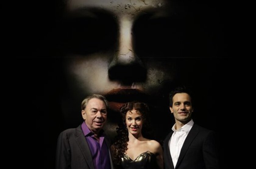 "British composer Andrew Lloyd Webber, left, stands with Iranian-born Canadian Ramin Karimloo, right, who plays the Phantom, and Sierra Boggess from U.S., who plays Christine Daae, as they promote his new production ""Love Never Dies"" at a theater in London, Thursday Oct. 8, 2009. The new musical continues the story of ""The Phantom of the Opera"". (AP Photo/Matt Dunham)"