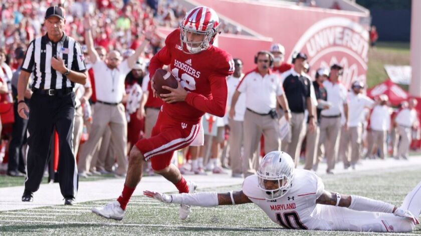 Indiana quarterback Alexander Diamont avoids a tackle attempt by Maryland defensive back Josh Woods