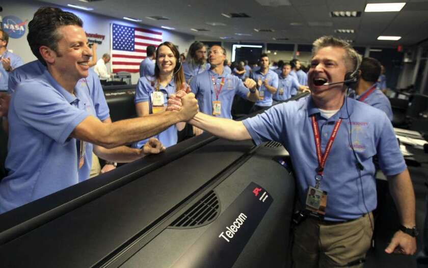 Flight director Keith Comeaux, right, and Martin Greco are jubilant in JPL's mission control room, which erupted in cheers after receiving word of Curiosity's successful landing on Mars.