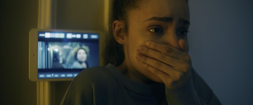 "Sofia Carson stands in front of a small video screen with her hand clasped over her mouth in ""Songbird."""
