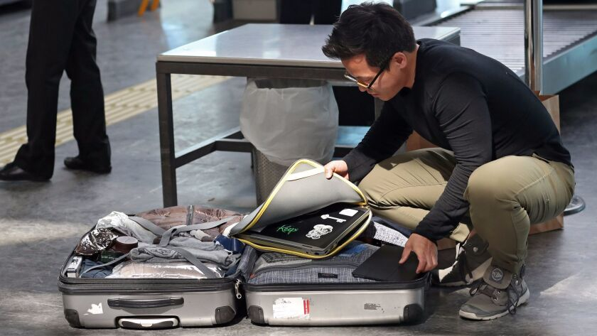 A passengers opens his luggage to show electronic equipment at a security point at Ataturk Airport, in Istanbul, Turkey.