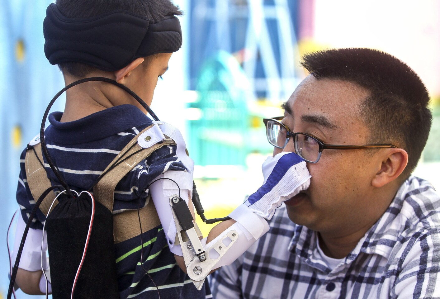 Five-year-old Max Ng, whose arms are paralyzed due to acute flaccid myelitis, is able to grab the nose of his father Ted Ng, thanks to a custom motorized orthotic brace that mechanical engineering undergraduate students at UC San Diego have created, during a demonstration of the brace at Rady Children's Hospital on Friday, June 14, 2019 in San Diego, California.
