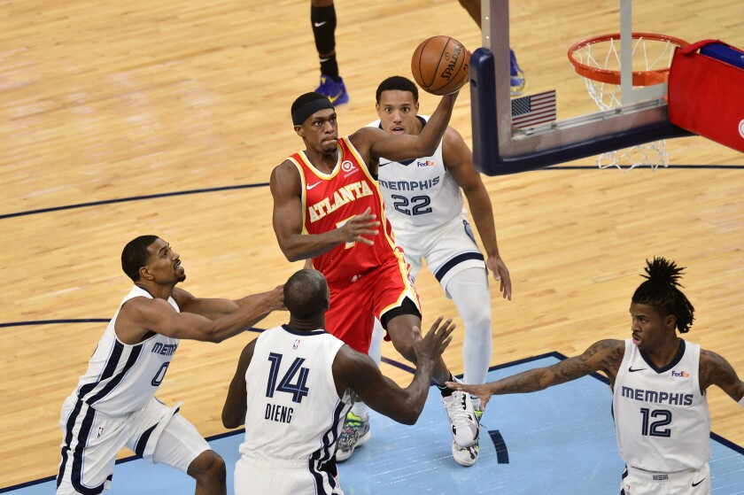 Atlanta Hawks guard Rajon Rondo (7) drives to the basket between Memphis Grizzlies center Gorgui Dieng (14) and guards De'Anthony Melton (0), Ja Morant (12) and Desmond Bane (22) in the second half of an NBA preseason basketball game Thursday, Dec. 17, 2020, in Memphis, Tenn. (AP Photo/Brandon Dill)