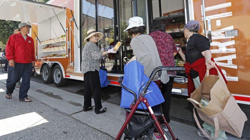 Village Center Apartments senior citizens pick through fresh, nutritious foods during the Park-It Ma