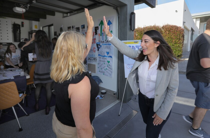Congressional candidate Sara Jacobs, right, greets campaign volunteer Karen Grossman at the Solana Beach home of supporters Nora and Brad Shoen before Karen and others left to canvas voters during Jacobs' unsuccessful 2018 bid for Congress.
