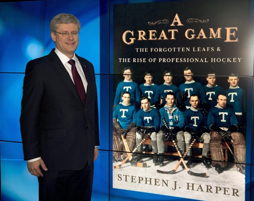 "Canada Prime Minister Stephen Harper poses with a projected image of his book ""A Great Game"" during an appearance on a morning breakfast television show in Toronto on Monday, Dec. 2, 2013. (AP Photo/The Canadian Press, Frank Gunn)"