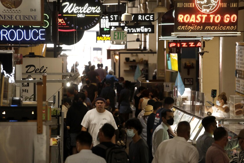 People, many of them masked, wait for lunch at the Grand Central Market in downtown Los Angeles on June 15.